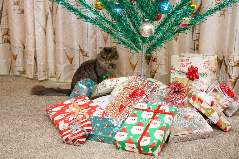 A fluffy grey cat sits under a green aluminum tree surrounded by presents.