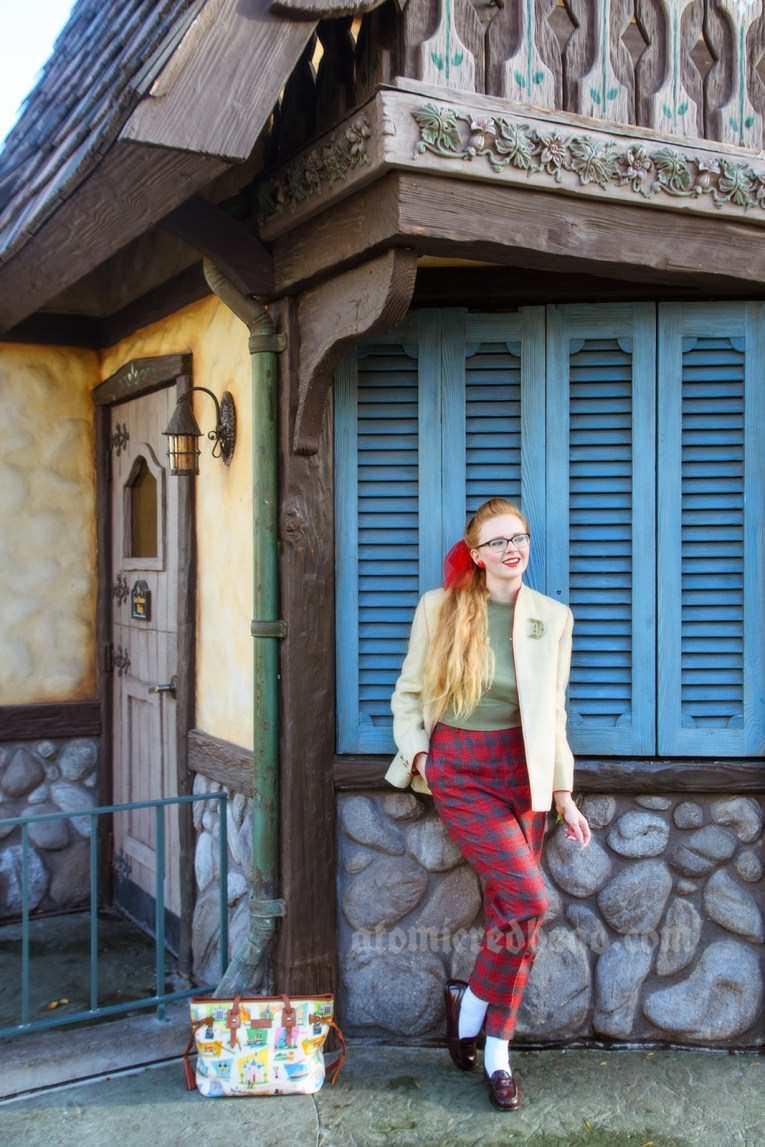 Myself standing near a blue shuttered building inspired by the Swiss Alps, wearing a cream jacket, a green sweater and red and grey plaid pants. My hair is in a ponytail, tied with a red scarf. A red brooch featuring small ice skates is pinned to my sweater.