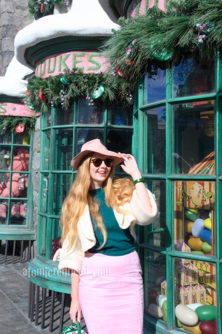 Myself standing outside of Honeydukes. Windows filled with candy. I'm wearing a pink fedora, white bolero jacket, forest green sweater, and a pink pencil skirt.