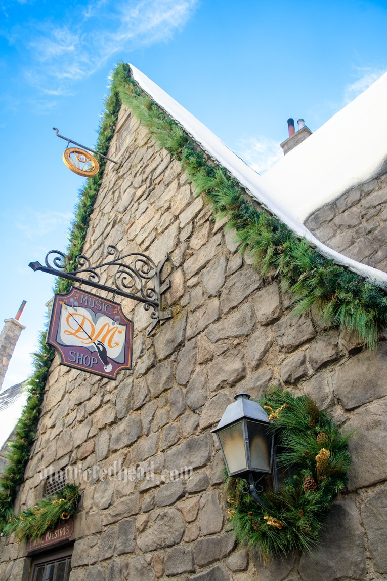 Grey stone walls of Hogsmeade, with green garlands along the roof edges.