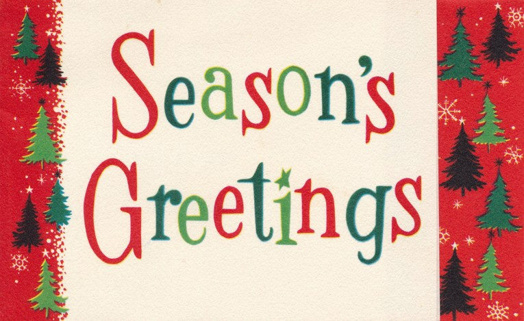 """A white card is edged in red with small green trees on each side. In the center, it reads """"Season's Greetings"""""""