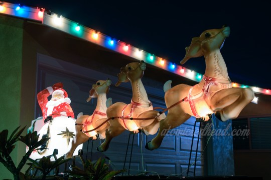 Santa waves from his sleigh full of toys as he appears to take off, pulled by three reindeer.