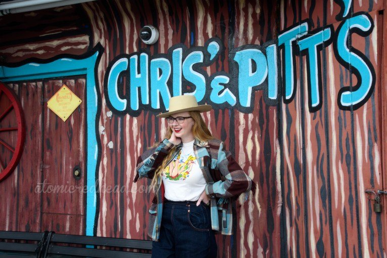 "Myself standing outside against the amazing faux painted wood side, with ""Chris & Pitt's"" painted in large turquoise letters. I'm wearing wide leg jeans, brown cowboy boots, a cream shirt featuring a cowgirl pin-up who has been bucked off a horse, a blue and brown plaid jacket, and a cream cowboy hat."