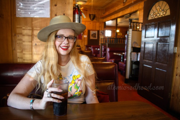 Myself seated inside Chris & Pitt's, with its wood paneling and various western themed items scattered on the wall.