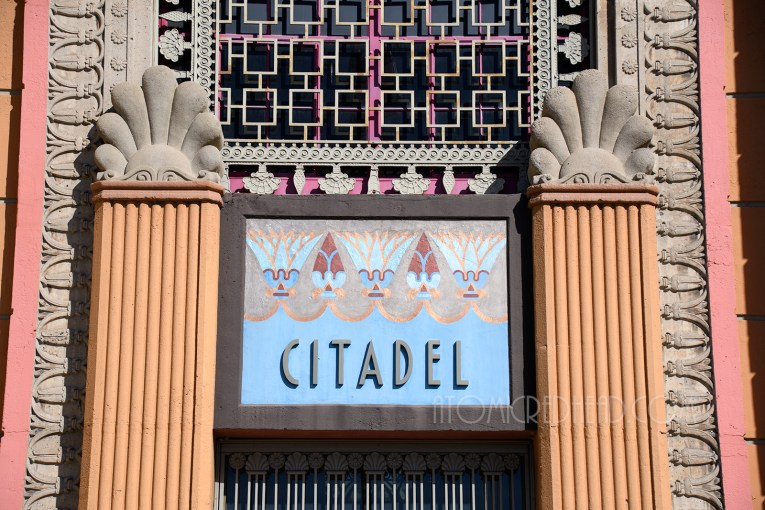 """Close-up of the sign above the main doors, a blue sign reading """"CitadeL"""" with tan and maroon lotus flowers."""