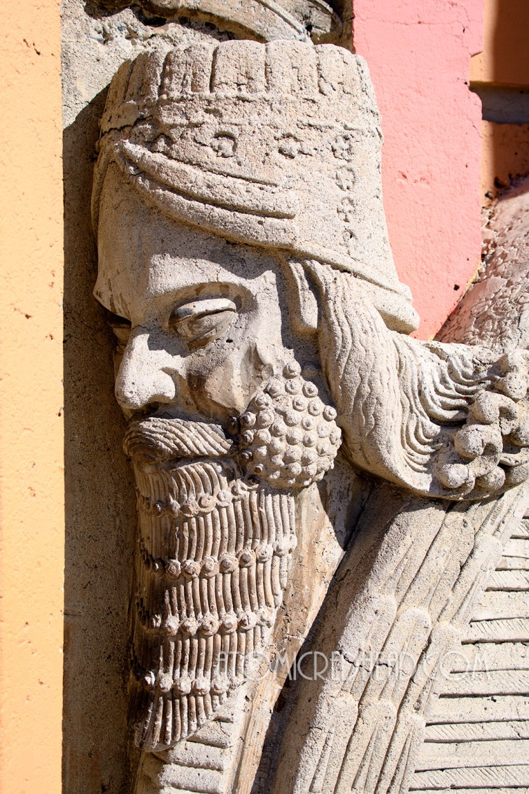 Close-up of the face of one of the Lamassu creatures that sit outside the door. He has a tall crown like hat and beard, and curly long hair.