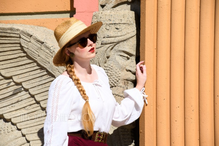 Myself standing outside the main doors, wearing a straw hat, a white peasant top, and maroon skirt that features gathering in an asymmetrical design.