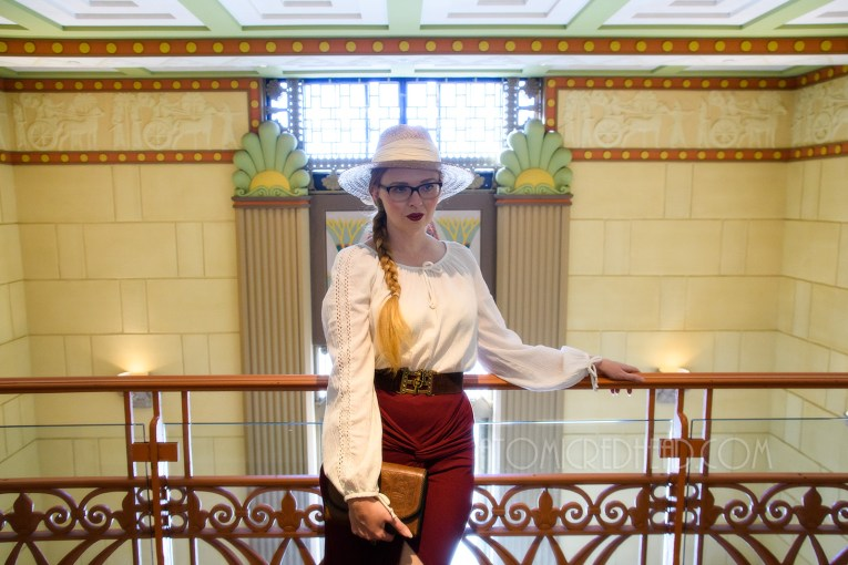 Myself standing inside, on the balcony, wearing a straw hat, a white peasant top, and maroon skirt that features gathering in an asymmetrical design.