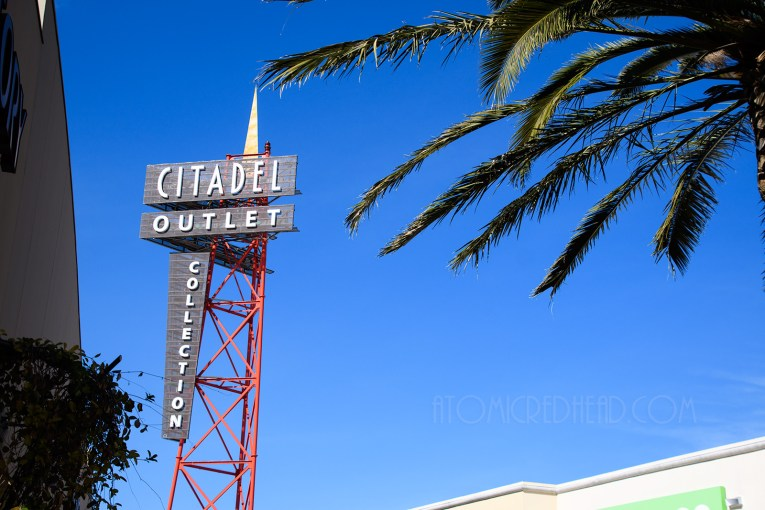 "A tall metal sign reading ""Citadel Outlet Collection"""
