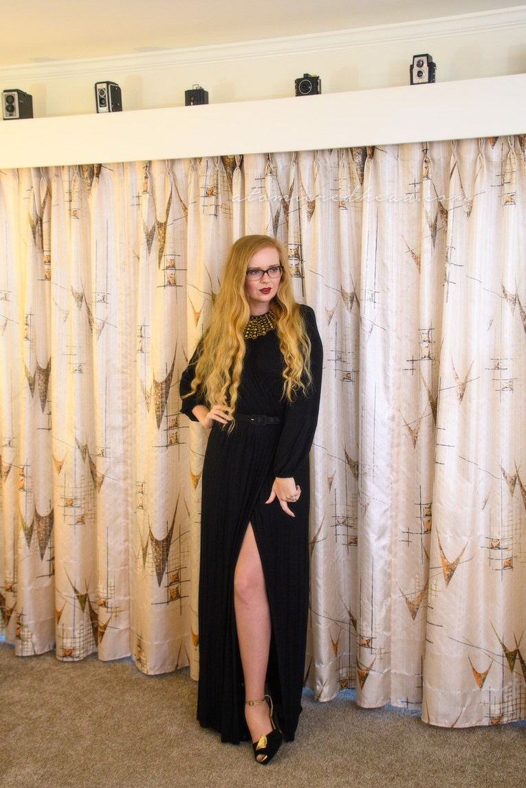 Myself wearing a long sleeve, full length black dress, with a slit up the side, wearing an art decor fan style necklace of gold rhinestones.
