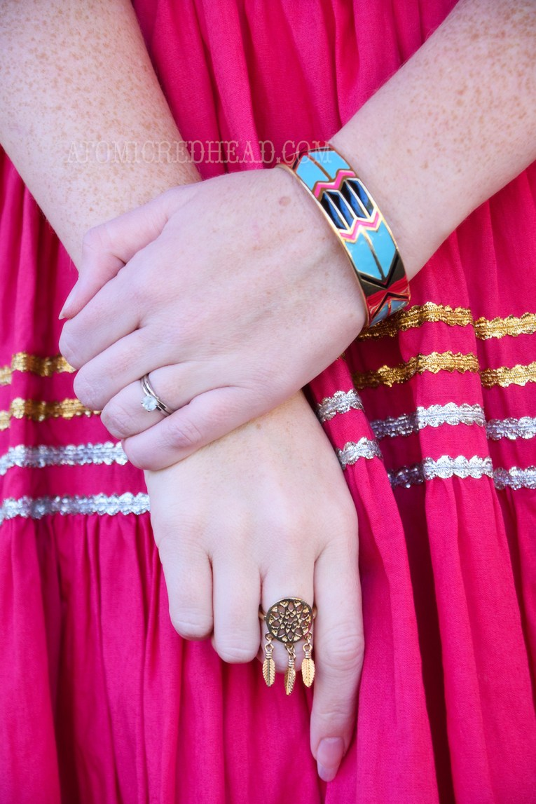 Close-up of my bracelet, which is gold and features zig-zag and stripe pattern in blue, black, and magenta, and a gold ring shaped like a dreamcatcher.