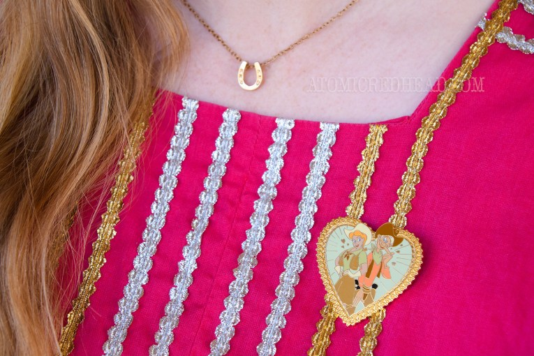 Close-up of my necklace, which is a gold horseshoe, and pin, which is heart-shaped and features Slue Foot Sue and Pecos Bill.