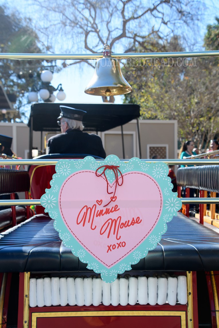"A pink heart edged in blue reads ""Minnie Mouse xoxo"" and is tied to the back of a vintage fire engine that drives up and down Main Street."