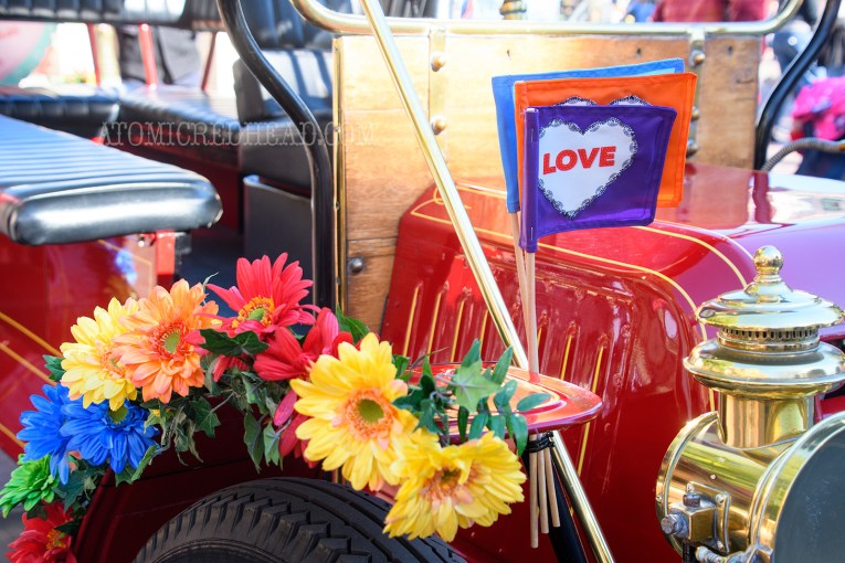 """Colorful flowers and a trio of flags featuring hearts reading """"love"""" are attached to the fender of one of the horseless carriages of Main Street."""