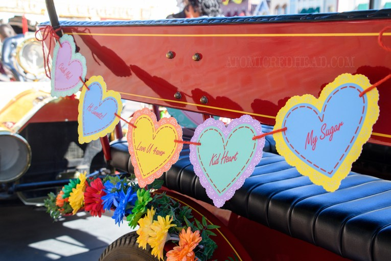 "A garland of different colored hearts hang on one of the horseless carriages of Main Street, reading ""Catch Me"" ""Hi Sweets"" and more."