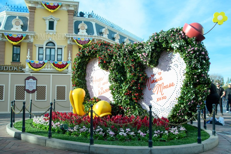 "In the middle of Town Square a massive double heart valentine sits, edged in green leaves reads ""Hugs & Kisses Minnie Mouse xoxo"""