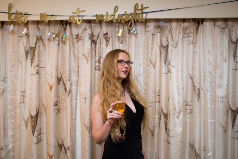 "Myself standing in front of a mid-century modern abstract print curtain in a black dress, a rhinestone necklace, in the background a banner reads ""Kiss me at midnight"" in gold glitter."