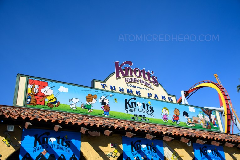 "Above the gates to Knott's Berry Farm a large banner featuring various members of the Peanuts Gang and text reading ""Knott's Berry Farm Peanuts Celebration"""