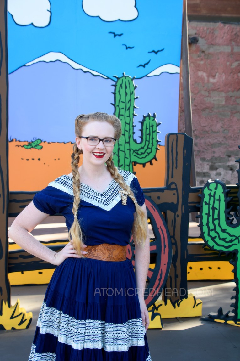 Myself, in front of a Peanuts style backdrop of a desert scene, wearing a navy colored patio set with silver ric-rac trim, and a tooled leather belt, purse, and shoes.