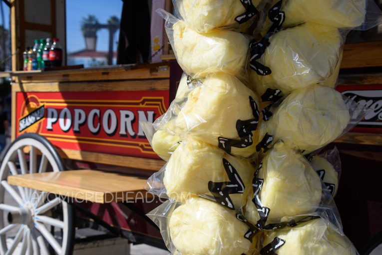 Nearby a popcorn cart, yellow cotton candy has been wrapped in a clear bag with a black zig-zag design to emulate Charle Brown's shirt.