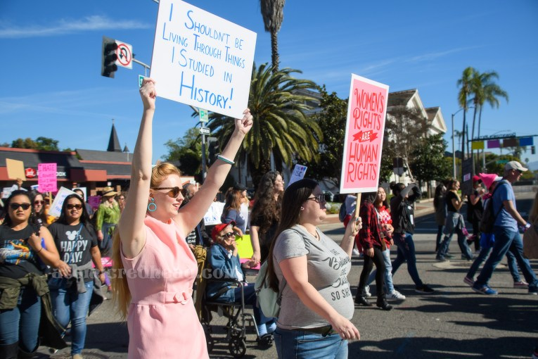 "Myself, wearing a pink mini dress and blue scarf carrying a sign reading ""I Shouldn't Be Living Through Things I Studied in History"" along side my friend Kaitlyn who wears a shirt reading ""She Believed She Could So She Did"" and carrying a pink sign reading ""Women's Rights are Human Rights"""