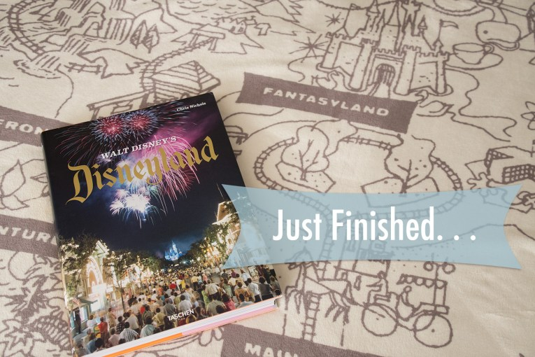 The book, Walt Disney's Disneyland, features a cover of a crowd watching fireworks from Main Street, sits upon a blanket featuring a drawn make of Disneyland.