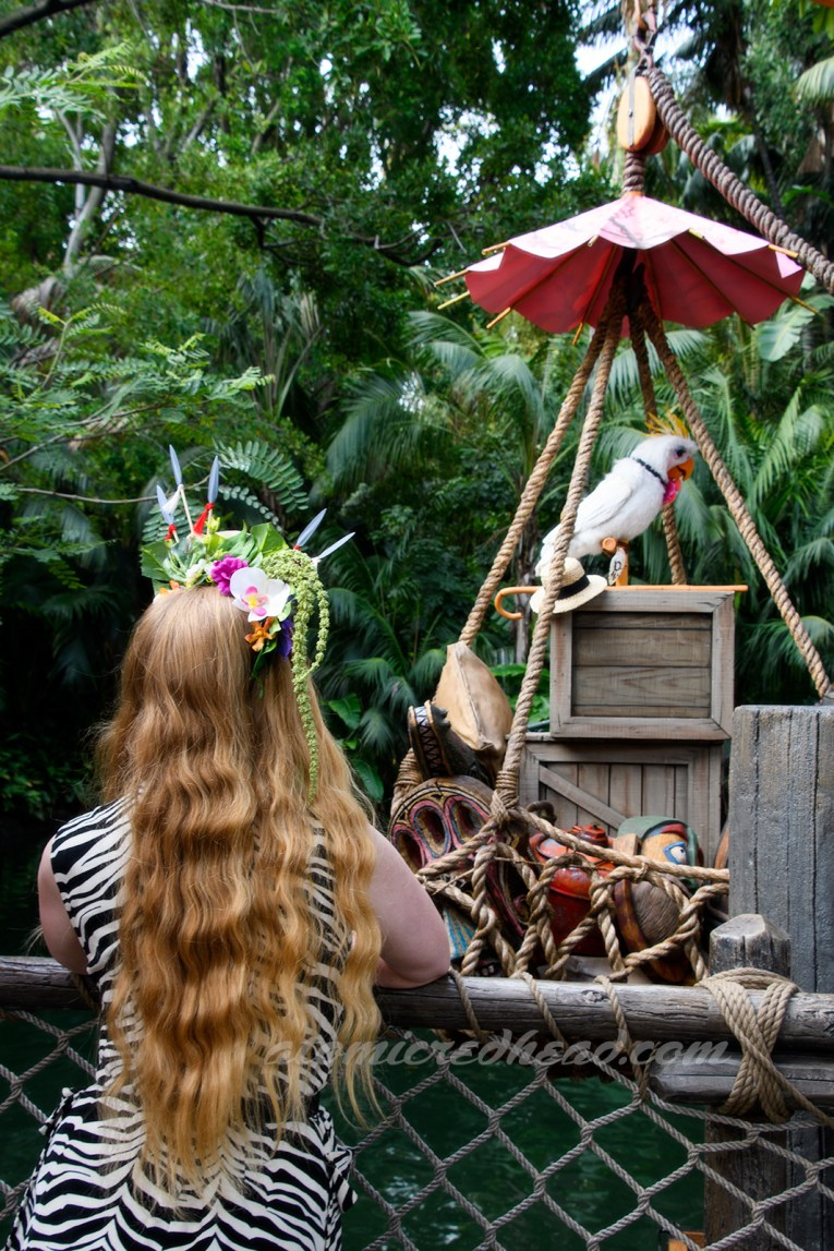 Myself, facing toward to water of the Jungle Cruise, looking at Rosita, a white bird atop a shipping crate.