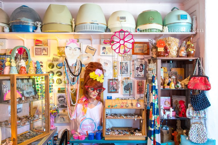 Just inside the Beauty Bubble. A shelf along the top features vintage hair dryers.The walls are covered with various hair items, curlers, bobby pins and hair pin cards, there are shelves with vintage jewelry for sale.