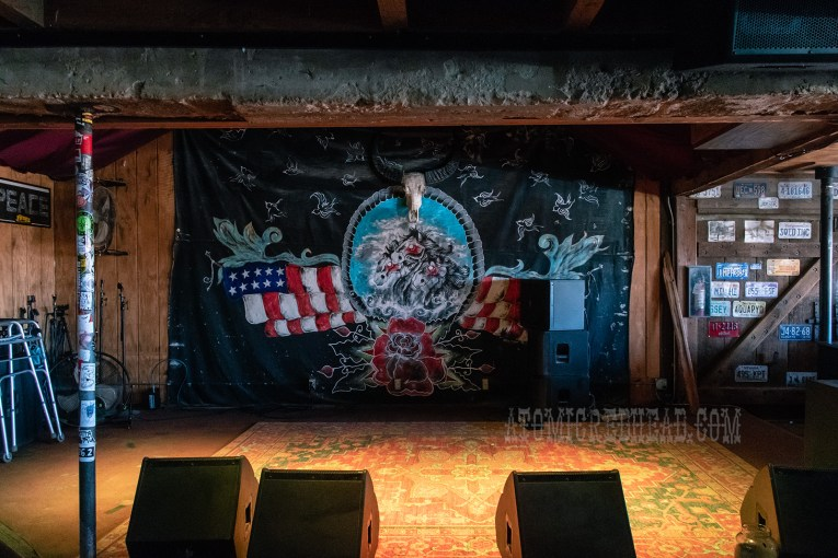 The stage of Pappy & Harriet's, featuring a painting of horses and the American flag.