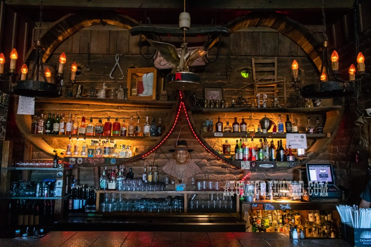 The bar of Pappy & Harriets, with shelves lined with bottles, a carved wood bust of Pappy sits in the middle.