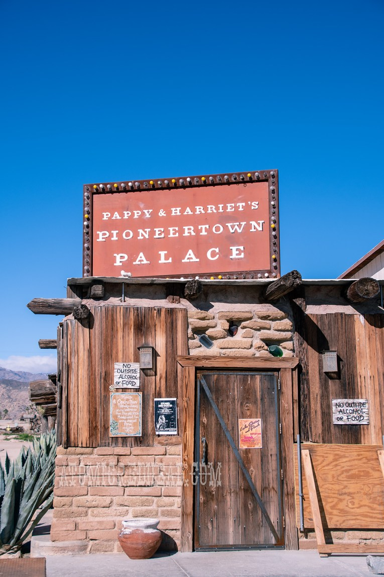 """Exterior of Pappy & Harriets, a stucco and wood rustic western building with large agave plants growing on the edge. A large sign rising above the front door reading """"Pappy & Harriet's Pioneertown Palace"""""""