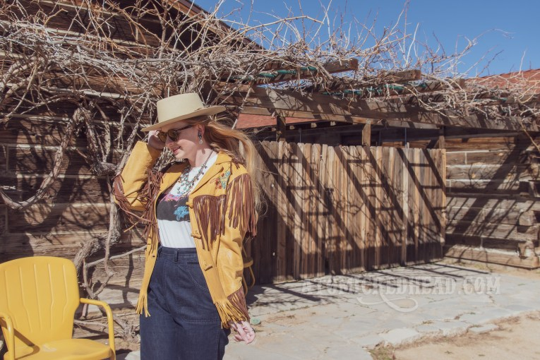 "Myself standing in front of part of the Pioneertown Motel, wearing a butter yellow leather jacket with dark brown fringe, a t-shirt featuring the cover of the Eagles' album ""Hotel California,"" jeans, and a cream colored flat top cowboy hat."