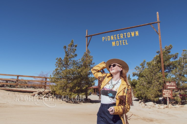 """Myself standing in front of the Pioneertown Motel sign, wearing a butter yellow leather jacket with dark brown fringe, a t-shirt featuring the cover of the Eagles' album """"Hotel California,"""" jeans, and a cream colored flat top cowboy hat."""