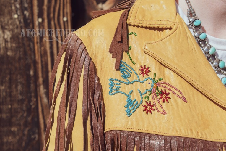 Close up of the front of my jacket, which features a beaded blue bird with a pink ribbon and red flowers in its beak.