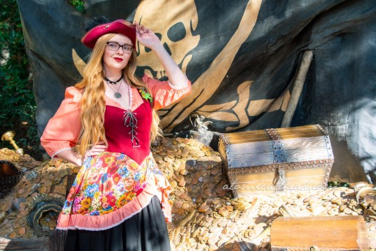Myself, wearing a dress with peach sleeves, maroon corset, and floral skirt, worn over a black skirt to the knee, and a maroon pirate hat, standing in front of a large pile of gold and other treasures, and a massive pirate flag.