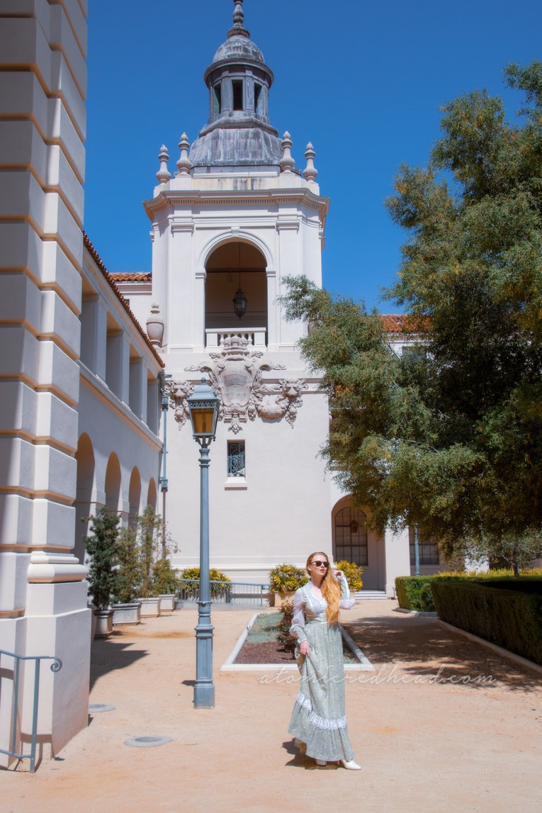 Inside the courtyard of Pasadena City Hall, with towers at the corners, wearing a long pale green dress with small white flowers.