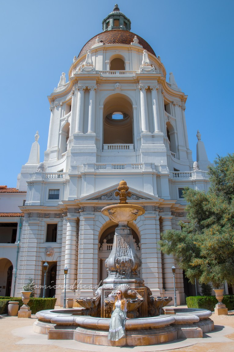 Inside the courtyard of Pasadena City Hall, with towers at the corners and a fountain, wearing a long pale green dress with small white flowers.