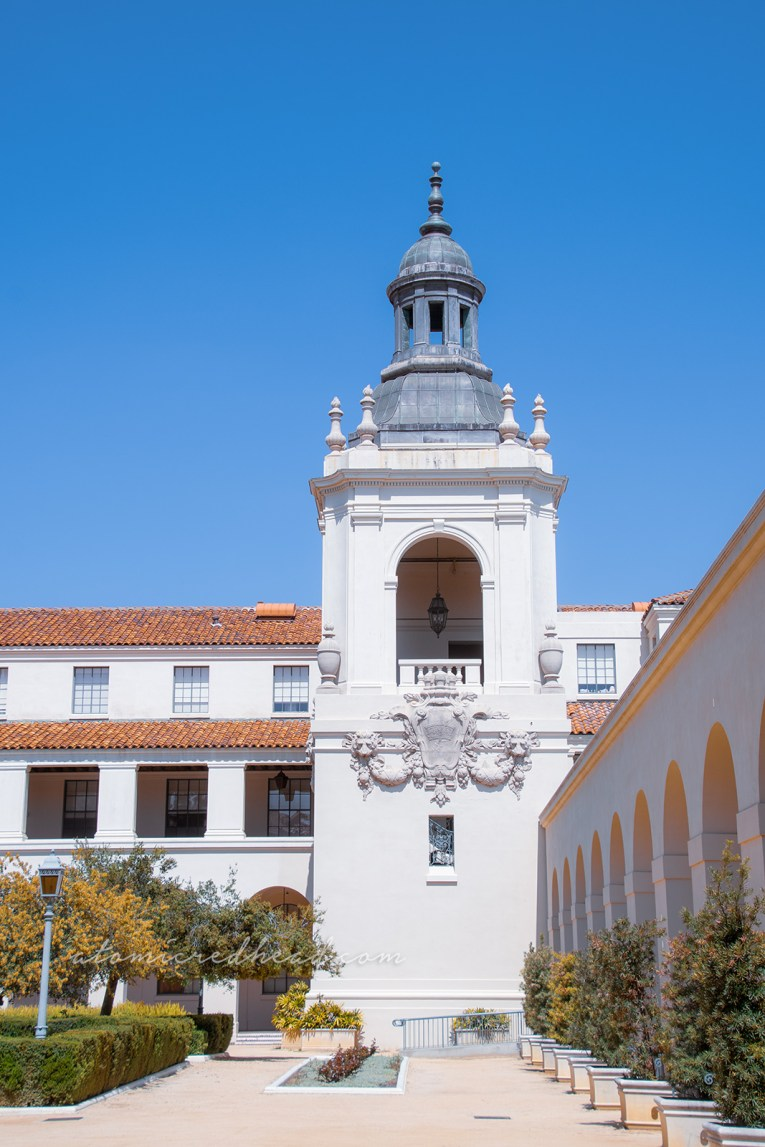 The corners of Pasadena City Hall each feature a tower, with arched openings and scroll and shield work below them.