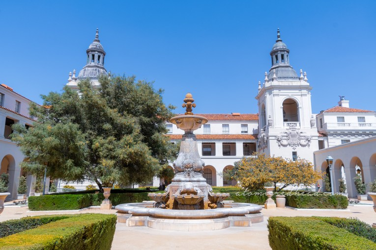 The courtyard of Pasadena City Hall, with a fountain in the middle and low, clean cut green hedges around.