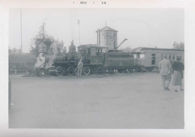 A black and white photo of the train at Knott's Berry Farm, with a wooden water tower behind it.