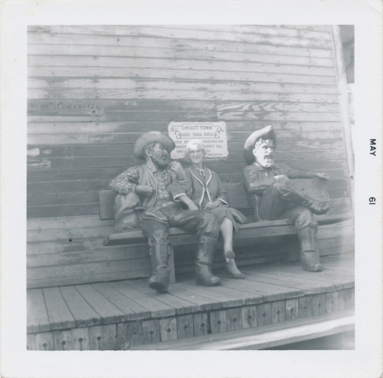 A black and white photo of of an older woman sitting next to the cowboy statues at Knott's.