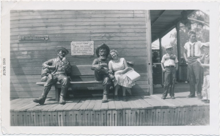 A black and white photo of a woman in a dress with the cowboy statues.