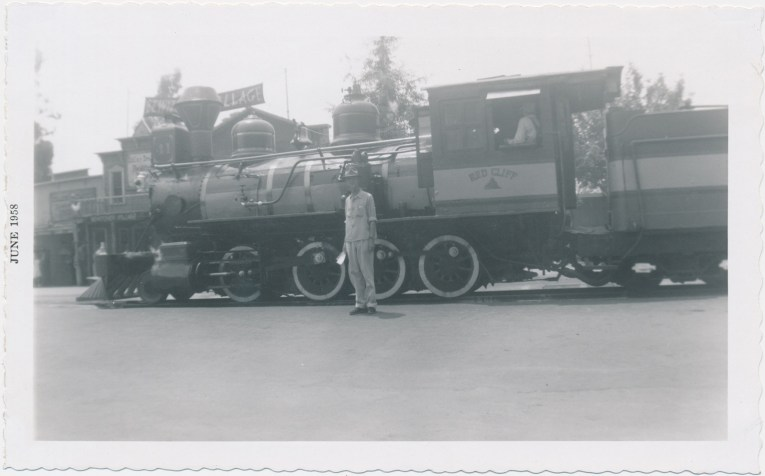 A black and white photo of the train at Knott's, with one of the engineers standing out front.