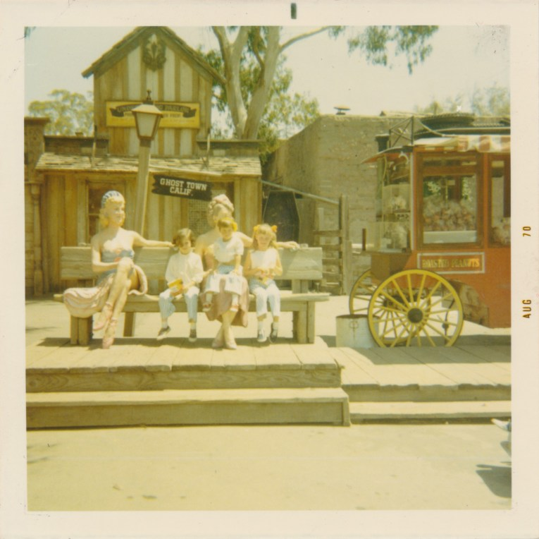 A color photo of girls sitting with the statues of saloon girls in front of an undertaker building.