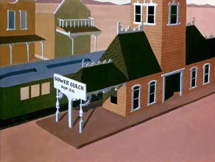"An animated old west railroad station with a sign reading ""Gower Gulch Pop. 86"""