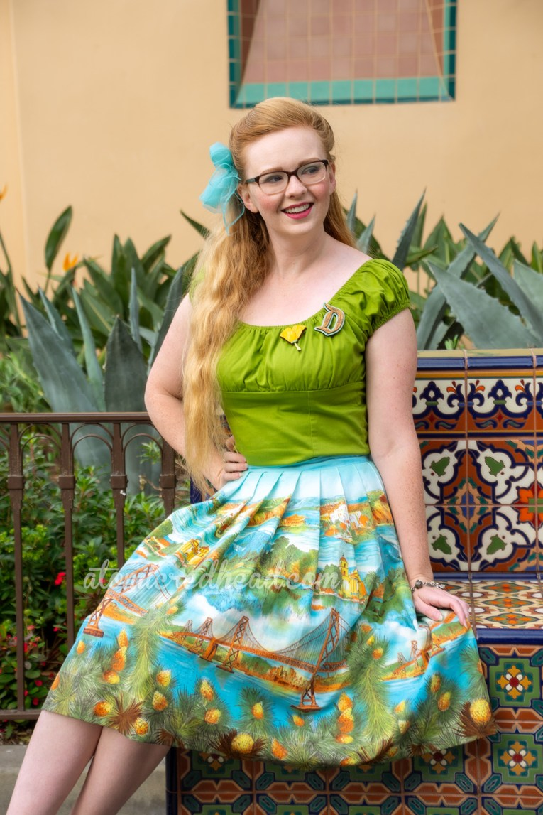 Myself sitting on a mosaic tile bench, wearing a green peasant top, with a D shaped brooch, and a poppy flower brooch, and a skirt featuring images of the San Fransisco-Oakland Bay Bridge, Catalina, and Mission Santa Barbara, a blue scarf is tied in my hair, and yellow shoes.
