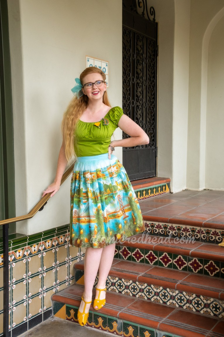 Myself standing on mosaic tile steps leading up to a wrought iron gate, wearing a green peasant top, with a D shaped brooch, and a poppy flower brooch, and a skirt featuring images of the San Fransisco-Oakland Bay Bridge, Catalina, and Mission Santa Barbara, a blue scarf is tied in my hair, and yellow shoes.