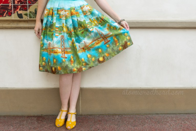 A shot from the waist down, my hand holding out the skirt, displaying illustrated images of Catalina, Mission Santa Barbara, and the San Fransisco-Oakland Bay Bridge, Joshua trees in bloom along the hem of the skirt.