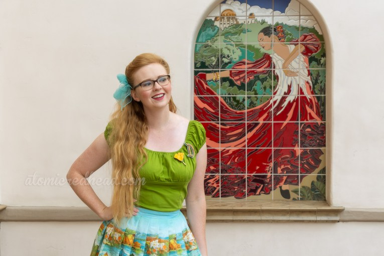 Myself standing in front of a mosaic image of a female Spanish dancer in a red dress, wearing a green peasant top, with a D shaped brooch, and a poppy flower brooch, and a skirt featuring images of the San Fransisco-Oakland Bay Bridge, Catalina, and Mission Santa Barbara, a blue scarf is tied in my hair, and yellow shoes.