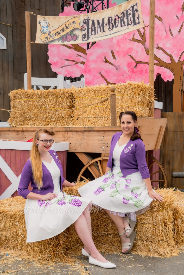 Kiley and I sitting on hay bales wearing the same thing, a purple sweater over a white dress with painted boysenberries.